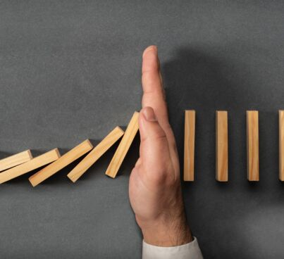 hand stopping falling dominoes as mood image for online risk management section